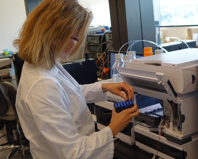 technologist loading samples into a liquid chromatography mass spectrometer for drug analysis